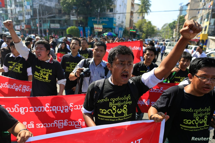 FILE - Reporters shout as they march demanding broader press freedom in Yangon, Myanmar, Jan. 7, 2014.