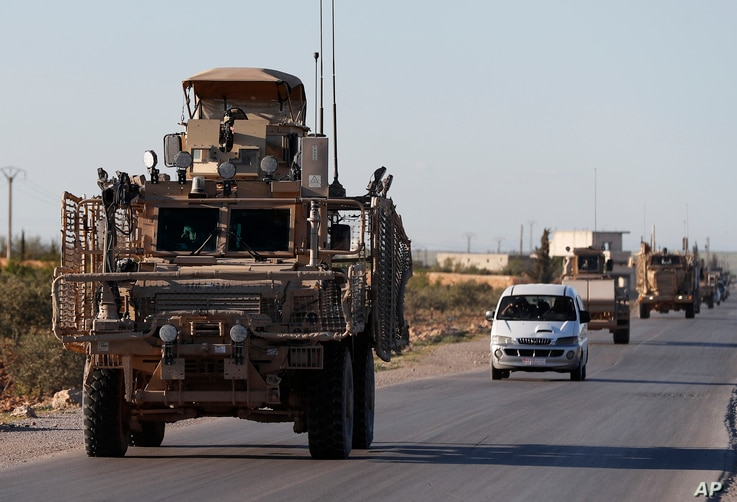 A convoy of U.S. troops drive on a road leading to the tense front line with Turkish-backed fighters, in Manbij, north Syria, March 31, 2018.