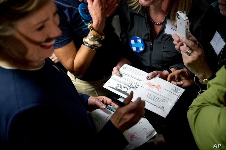 Democratic presidential candidate Hillary Clinton signs a vote-by-mail ballot letter as she greets volunteers at a campaign field office in San Francisco, Oct. 13, 2016.