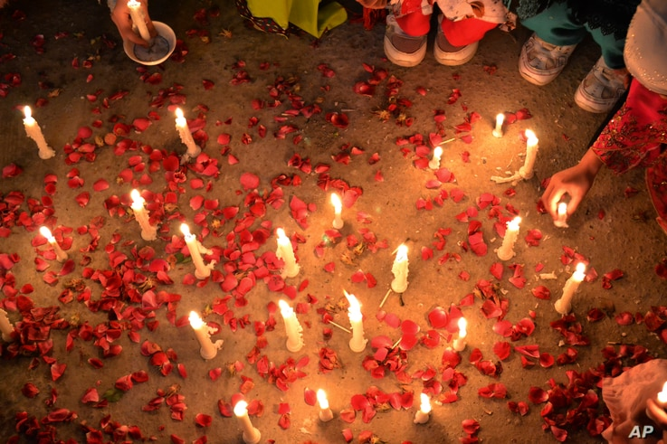 Pakistani children hold candles during a vigil to condemn the attacks on their ethnic Hazara community, in Quetta, Pakistan, Feb. 16, 2014.