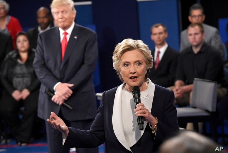 Democratic presidential nominee Hillary Clinton speaks as Republican presidential nominee Donald Trump reacts during the second presidential debate at Washington University in St. Louis, Oct. 9, 2016.