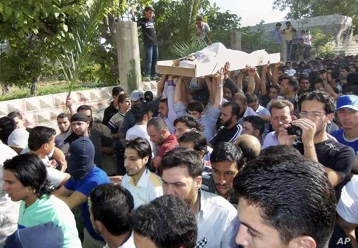 Anti-Syrian regime mourners chant slogans as they carry the body of soldier Khaled Shurbajy, who was shot by Syrian security forces in Dir el Zour last week after disobeying orders to fire on anti-Assad protesters, during his funeral procession, in t...