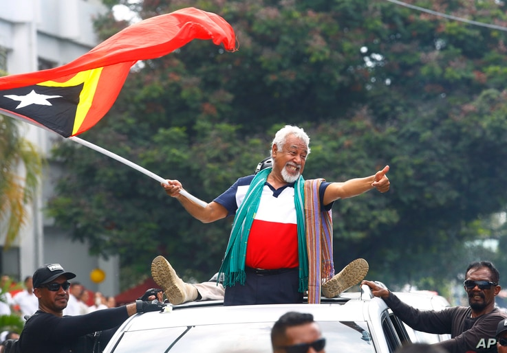 East Timorese independence hero Xanana Gusmao, center, waves a national flag upon arrival in Dili, East Timor, March 11, 2018.