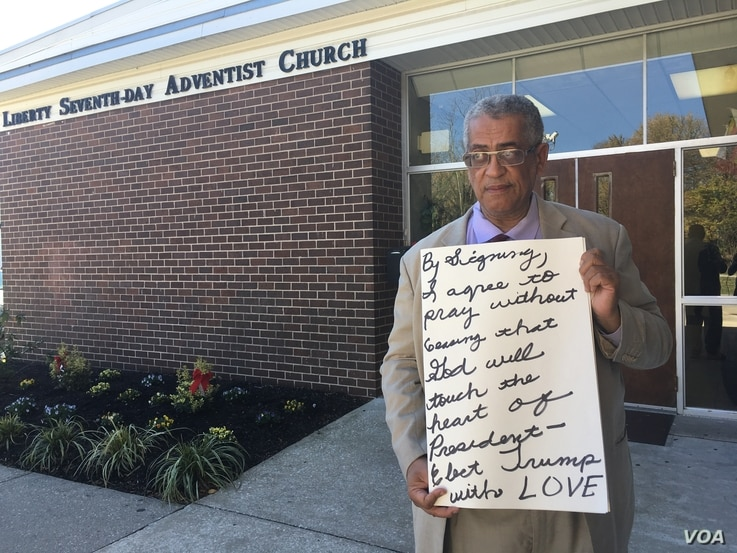 """Rocky Twyman solicits signatures on a card that reads: """"By signing, I agree to pray without ceasing that God will touch the heart of President-elect Trump with LOVE,"""" at Liberty Seventh-day Adventist Church in Baltimore, Maryland. (A. Arabasadi/VOA)"""