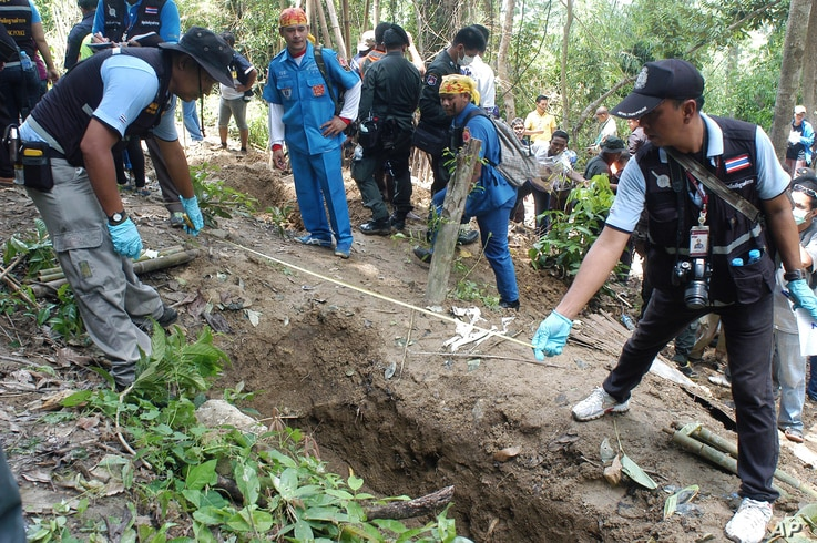 Thai policemen measure shallow graves in Songkhla province in southern Thailand, May 2, 2015.