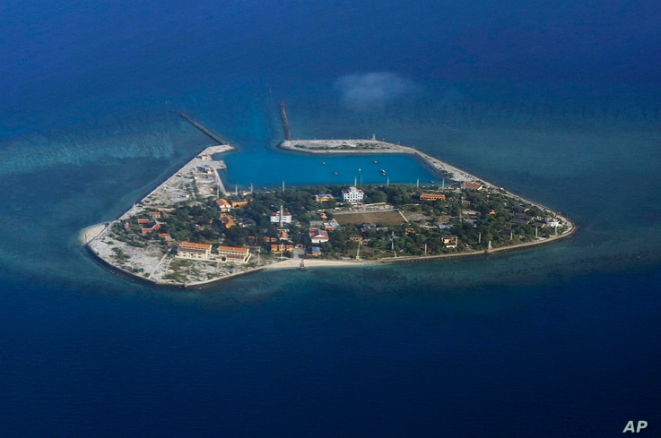 FILE - The Vietnamese-claimed Southwest Cay island in the Spratly island group is seen from a Philippine Air Force C-130 transport plane during the visit to the Philippine-claimed Thitu Island by Defense Secretary Delfin Lorenzana, Armed Forces Chief...