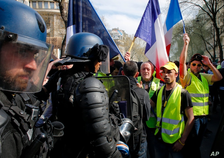 """Riot police stand by as French """"yellow vest"""" protesters rally, March 30, 2019, in Paris. The demonstrators are undeterred by protest bans or repeated injuries in 20 weeks of demonstrations."""