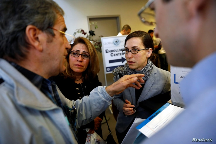 Hossein Khoshbakhty, left, speaks with attorney Talia Inlender about his Iranian family members effected by the travel ban as Homa Homaei, second from left, looks on outside the U.S. Customs and Border Protection office at Los Angeles International A...