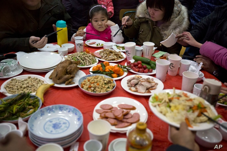 "A Chinese girl looks upon a table full of food during a ""1,000 people dumpling feast"" in Liuminying village on the outskirt of Beijing, China, Friday, Jan. 27, 2017."