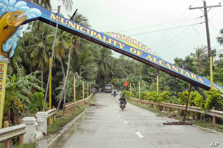 Motorists drive past a fallen marker that was toppled by Tropical Storm Jangmi at Alcantara township, Cebu province, central Philippines, Dec. 30, 2014.