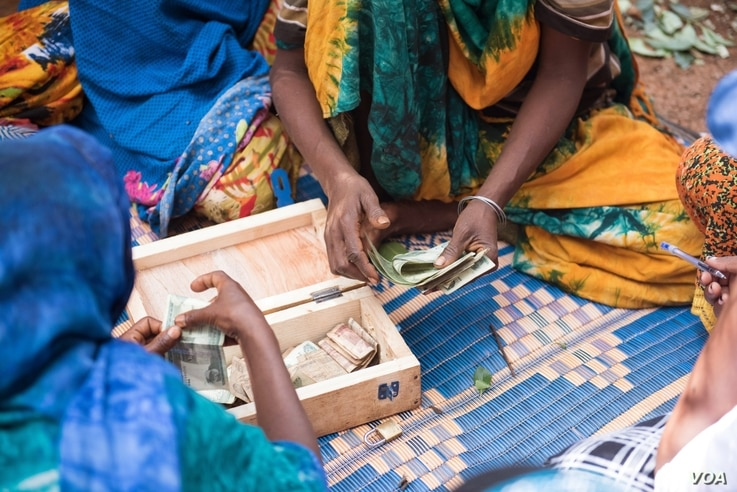 FILE - Women participate in a CARE Village Savings and Loan Association program in East Hararghe, Ethiopia. With a lockbox and some basic training, women can start small businesses and build financial independence. (Michael Tsegaye/CARE)