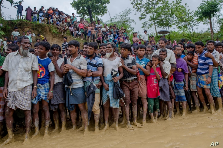 Rohingya Muslim men, who crossed over from Myanmar into Bangladesh, wait for their turn to collect food items distributed by aid agencies in Balukhali refugee camp, Bangladesh, Sept. 19, 2017.