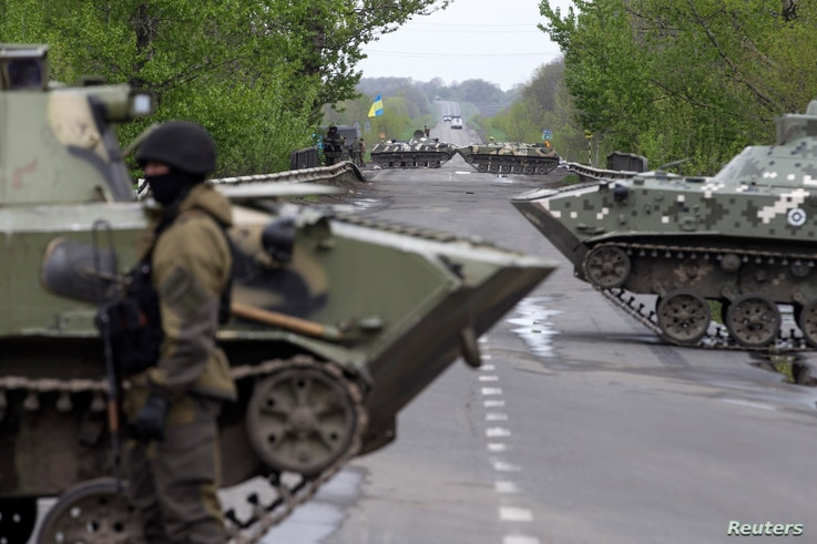 A Ukrainian soldier stands guard in front of armored personnel carriers at a check point near the village of Malinivka, southeast of Slaviansk, in eastern Ukraine, April 29, 2014