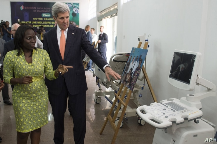 U.S. Secretary of State John Kerry and entrepreneur Patricia Nzolantima point at an ultrasound machine during a tour of a Sustainable Investment in Sub-Saharan Africa medical supply store in Kinshasa, DRC, May 3, 2014.