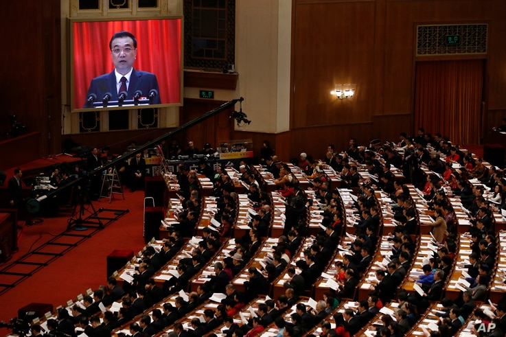 Chinese Premier Li Keqiang is shown on a large screen as he delivers a work report at the opening session of the annual National People's Congress at the Great Hall of the People in Beijing, March 5, 2018.