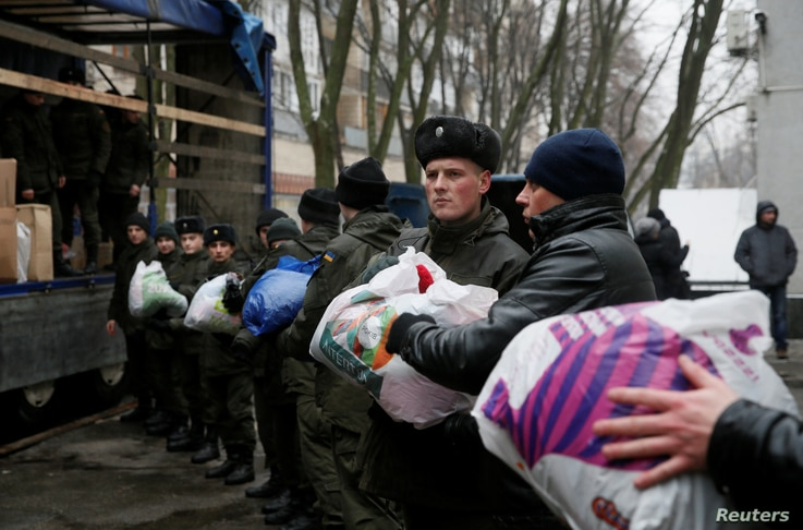 Members of the Ukrainian National Guard load humanitarian aid parcels for the government-held industrial town of Avdiyivka to a truck in Kyiv, Ukraine, Feb. 3, 2017.