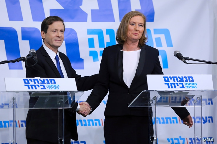 Issac Herzog (L), leader of Israel's Labour party, and former Justice Minister Tzipi Livin shake hands after their joint news conference in Tel Aviv, Dec. 10, 2014.