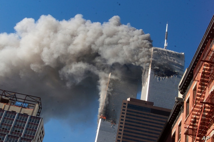 FILE - Smoke rises from the burning twin towers of the World Trade Center after hijacked planes crashed into them, in New York City, Sept. 11, 2001.
