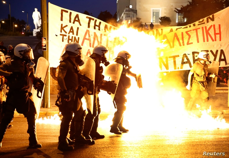 Riot police stand amongst the flames from exploded petrol bombs thrown by a small group of anti-establishment demonstrators in front of parliament in Athens, Greece July 15, 2015.