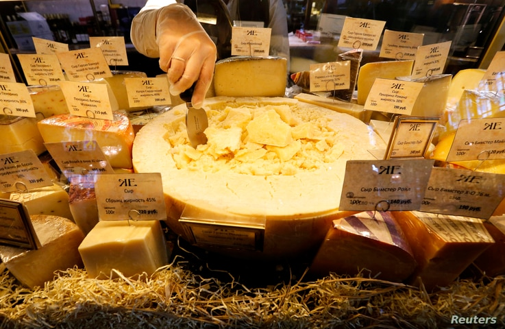 A worker arranges cheese for sale at a grocery store in St. Petersburg, Russia, Aug.11, 2014.
