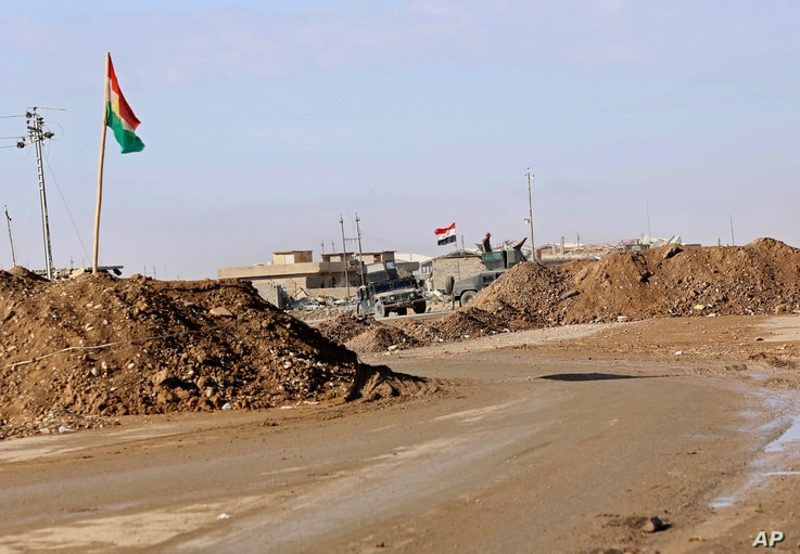 FILE - In this Dec. 3, 2016 photo, military vehicles guard an Iraqi Army checkpoint flying an Iraqi flag, center, next to a Kurdish checkpoint with a Kurdish flag, outside Irbil, northern Iraq.