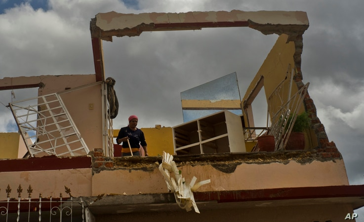 A woman works to recover belongings from her home destroyed by a tornado in Regla, Cuba, Jan. 28, 2019.