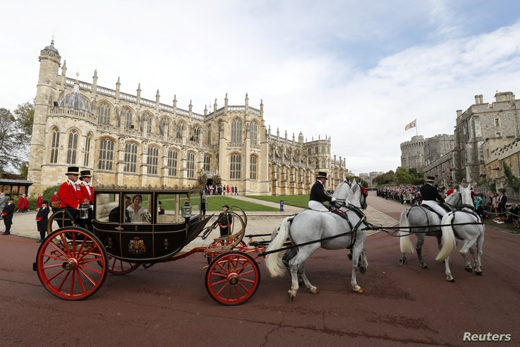 Britain's Princess Eugenie of York and her husband Jack Brooksbank travel in the Scottish State Coach at the start of their carriage procession following their wedding at St George's Chapel, Windsor Castle in Windsor, Britain, Oct. 12, 2018.