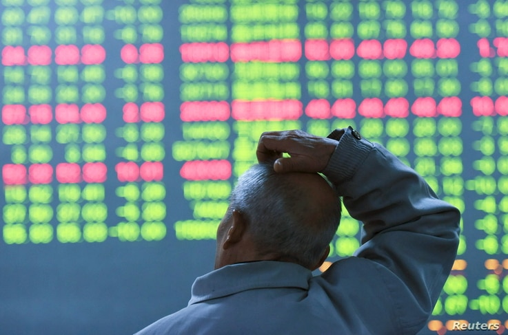 An investor looks at an electronic screen showing stock information at brokerage house in Hangzhou, Zhejiang Province, China, Jan. 11, 2016.