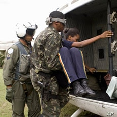 United Nations Stabilization Mission in Haiti (MINUSTAH) peacekeepers load an injured employee of Port-au-Prince's now-collapsed Hotel Montana onto a helicopter after a potent earthquake rocked the Haitian capital, 13 Jan 2010
