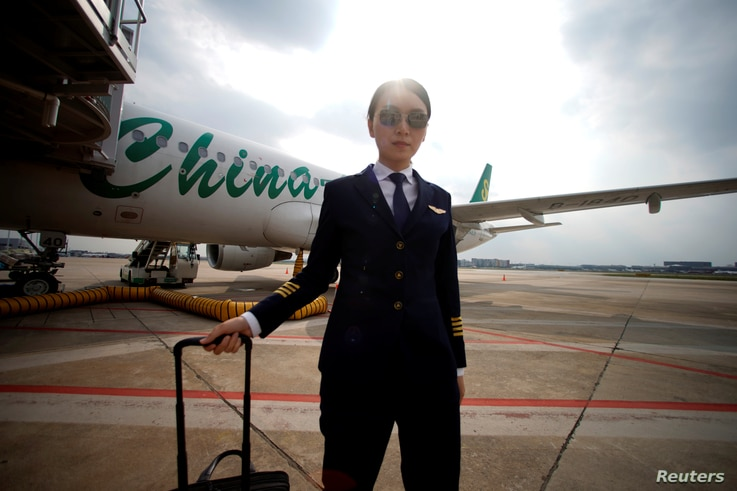 Captain Han Siyuan, 30, poses with Spring Airlines' Airbus A320 after landing at Hongqiao International Airport in Shanghai, China, Oct. 18, 2018.