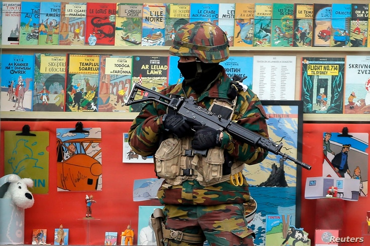 A Belgian soldier stands guard in front of a shop selling Tintin comic books in central Brussels, Belgium, March 24, 2016.