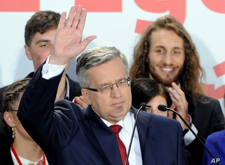 Polish President Bronislaw Komorowski waves to supporters as first exit polls are announced in Warsaw, Poland, May 24, 2015.
