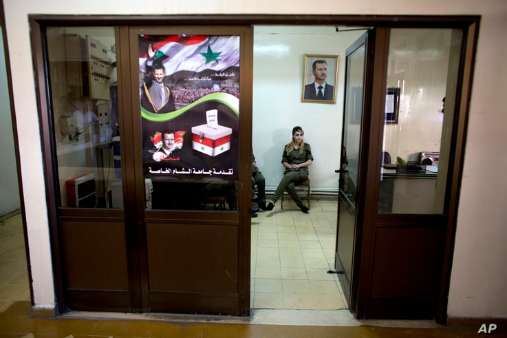 A Syrian soldier sits under the portrait of President Bashar al-Assad at a polling station in Damascus, June 3, 2014.