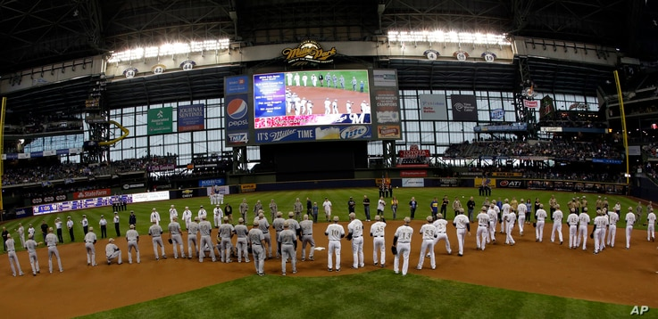 Members of the military throw out ceremonial first pitches to both teams before a baseball game between the Milwaukee Brewers and the Minnesota Twins in Milwaukee, May 27, 2013.