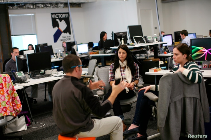 FILE - Facebook employees are seen gathered in their workspace for a discussion at Facebook headquarters in Menlo Park, California, Jan. 11, 2012.