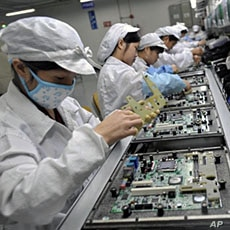 Chinese workers assemble electronic components at the Taiwanese technology giant Foxconn's factory in Shenzhen, Guangzhou province (File)