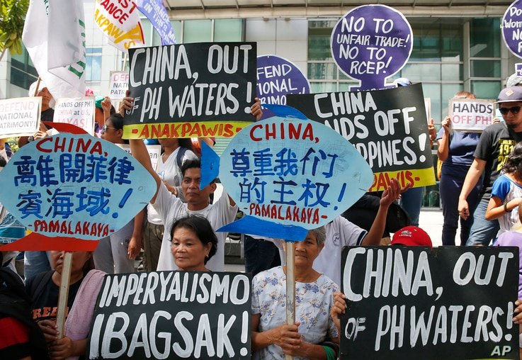 Protesters display placards during a rally at the Chinese Consulate to protest China's artificial island-building at the disputed islands, reefs and shoals off South China Sea, June 12, 2017 at the financial district of Makati city, east of Manila, P...
