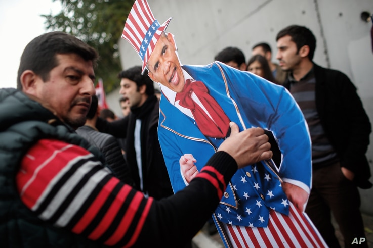 Plainclothes police officers take away an effigy of President Barack Obama as members of the Turkey Youth Union gather to protest the upcoming visit of Obama to Turkey in mid-November for G20 summit in Antalya, outside the US consulate in Istanbul, N...