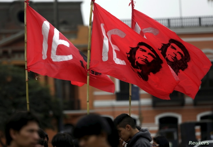 FILE - Protesters holding flags bearing the image of Che Guevara march during a mining national strike in Lima, May 21, 2015.