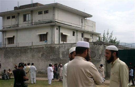 FILE - In this May 5, 2011 file photo, local residents and media are seen outside the house where al-Qaida leader Osama bin Laden was caught and killed in Abbottabad, Pakistan. Local residents say Pakistan has started to demolish the compound in the ...