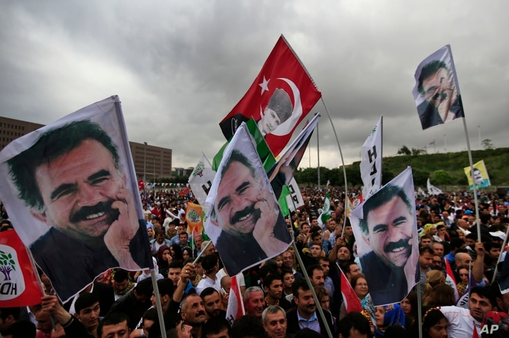 FILE - Supporters of the pro-Kurdish Peoples' Democratic Party, (HDP) wave a flag, center, with Turkish Republic founder Mustafa Kemal Ataturk, and others of imprisoned Kurdish rebel leader Abdullah Ocalan, during a rally in Istanbul, Turkey.
