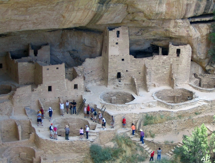 FILE - In this Aug. 27, 2005 photo, visitors tour Cliff Palace,an ancient cliff dwelling in Mesa Verde National Park, Colorado.