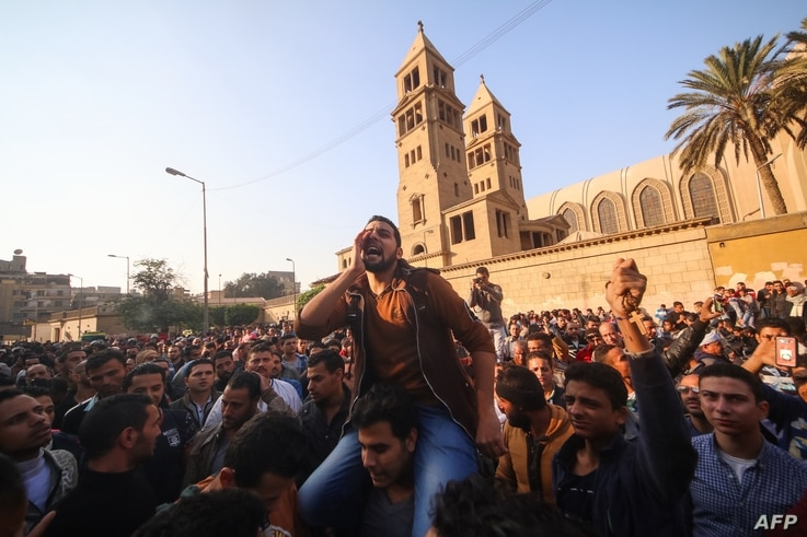 Egyptians shout slogans as they gather outside the the Saint Peter and Saint Paul Coptic Orthodox Church in Cairo's Abbasiya neighbourhood after it was targeted by a bomb explosion, Dec. 11, 2016.