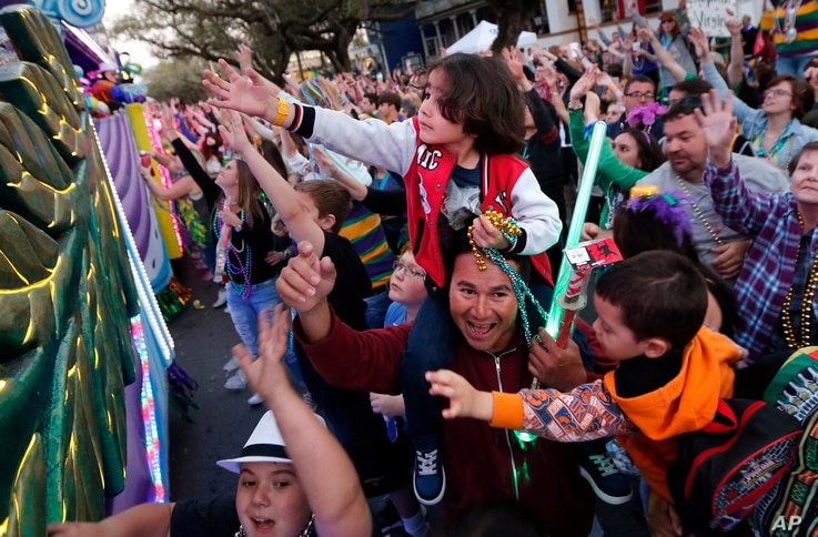 Revelers scream for beads during the Krewe of Endymion Mardi Gras parade in New Orleans, Saturday, Feb. 25, 2017.