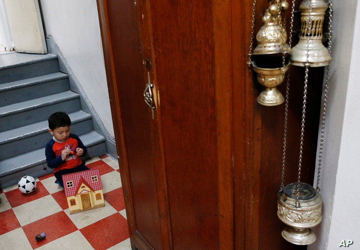 FILE - David Carvajal, 2, plays in the hallway of the Holyrood Episcopal Church in northern Manhattan, Oct. 26, 2017.
