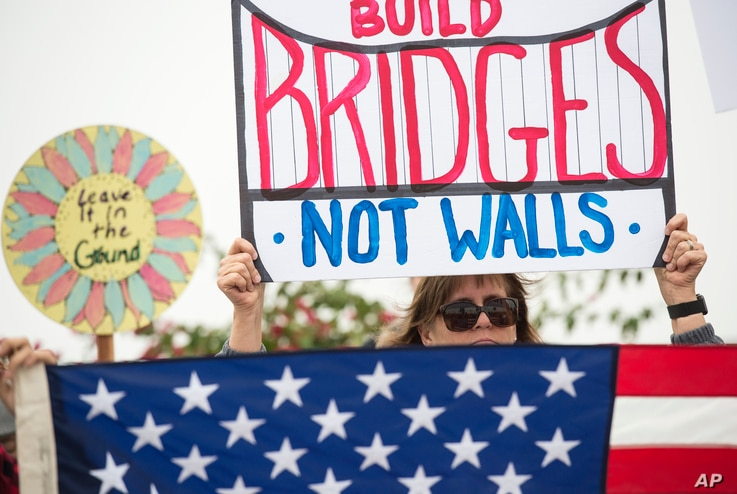 "Lauren Rees holds up a sign during a rally against a scheduled visit by President Donald Trump, March 13, 2018, in San Diego.  Protesters chanted, ""No ban! No wall!"" near the San Ysidro border crossing, where tens of thousands of people enter the..."