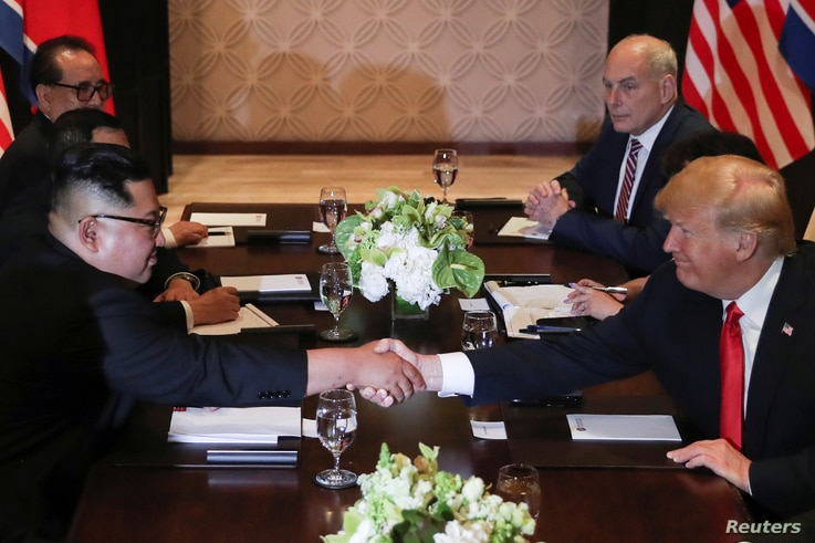 U.S. President Donald Trump and North Korea's leader Kim Jong Un shake hands during an expanded bilateral meeting at the Capella Hotel on the resort island of Sentosa, Singapore, June 12, 2018. With them are Senior North Korean Diplomat Ri Su Yong, t...