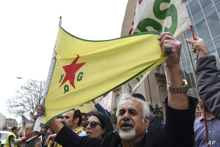 FILE - A man holds a flag of the YPG, a Syria-based Kurdish militant group, during a protest against Turkish President Recep Tayyip Erdogan in front of the Brookings Institution in Washington, where Erdogan was speaking, March 31, 2016.