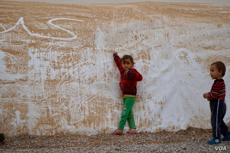 Two youngsters from Mosul play during a sandstorm in the Khazir camp for displaced civilians. (J. Dettmer/VOA)