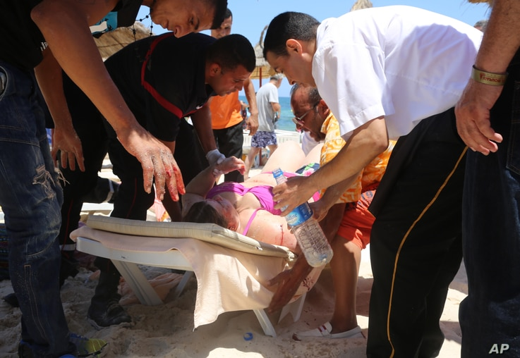 Injured people are treated after gunmen opened fire at beach near the Imperial Marhaba hotel in Sousse, Tunisia, June 26, 2015.